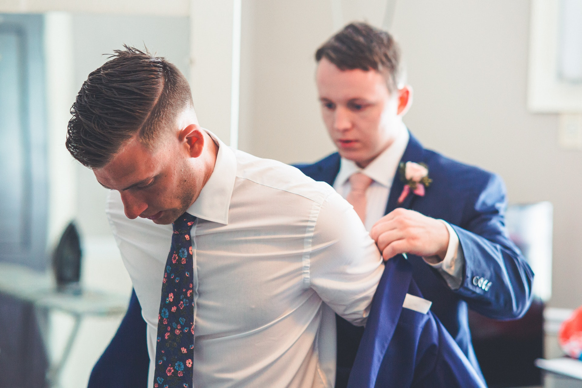 Groom putting on his formal coat