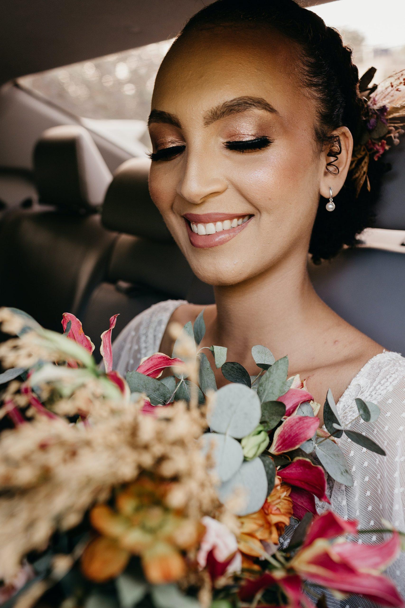 Bride smelling flowers in car